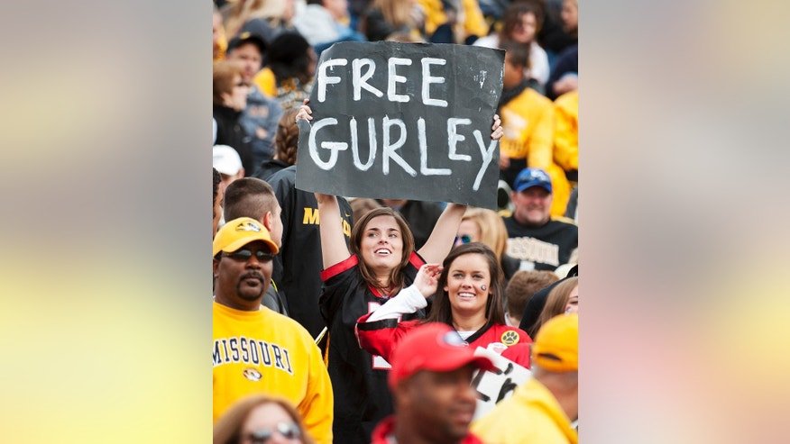 FILE - In this Oct. 11, 2014, file photo, a Georgia fan holds a sign in support of Georgia running back Todd Gurley who was suspended earlier this week, during the second quarter of an NCAA college football game against Missouri in Columbia, Mo. Georgia will file a request with the NCAA for Gurley's eligibility to be reinstated. Gurley has been suspended for the last two games while Georgia investigated allegations he broke NCAA rules by receiving improper benefits.(AP Photo/L.G. Patterson, File)
