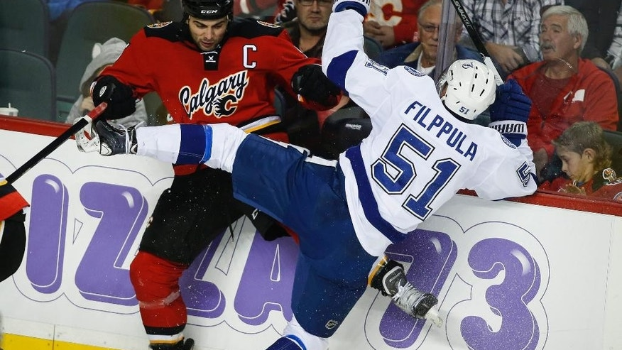 Tampa Bay Lightning's Valtteri Filppula, right, from Finland, checks Calgary Flames' Mark Giordano during the third period of an NHL hockey game Tuesday, Oct. 21, 2014, in Calgary, Alberta. Tampa Bay won 2-1 in overtime. (AP Photo/The Canadian Press, Jeff McIntosh)