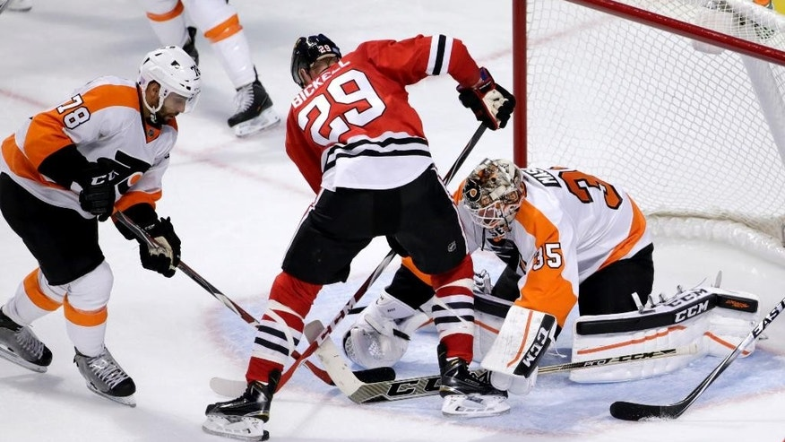 Philadelphia Flyers right wing Pierre-Edouard Bellemare (78) and goalie Steve Mason (35) keep Chicago Blackhawks left wing Bryan Bickell from getting a shot on goal during the second period of an NHL hockey game Tuesday, Oct. 21, 2014, in Chicago. (AP Photo/Charles Rex Arbogast)