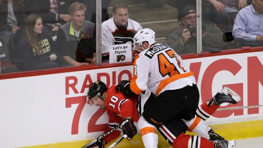 Philadelphia Flyers defenseman Andrew MacDonald (47) checks Chicago Blackhawks left wing Patrick Sharp into the boards during the second period of an NHL hockey game Tuesday, Oct. 21, 2014, in Chicago. (AP Photo/Charles Rex Arbogast)