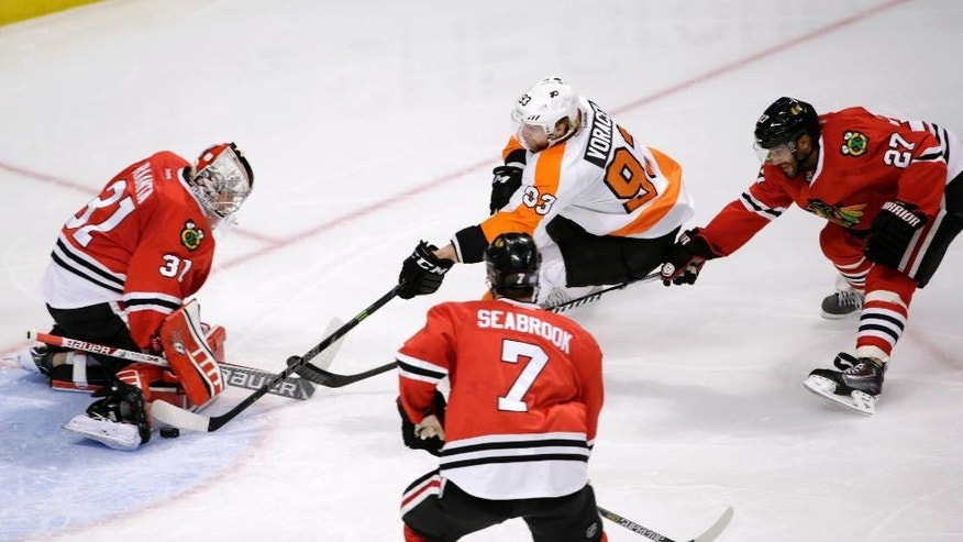 Chicago Blackhawks goalie Antti Raanta, left, makes a save on a shot by Philadelphia Flyers right wing Jakub Voracek, as Brent Seabrook (7) and Johnny Oduya (27) watch, during the second period of an NHL hockey game Tuesday, Oct. 21, 2014, in Chicago. (AP Photo/Charles Rex Arbogast)