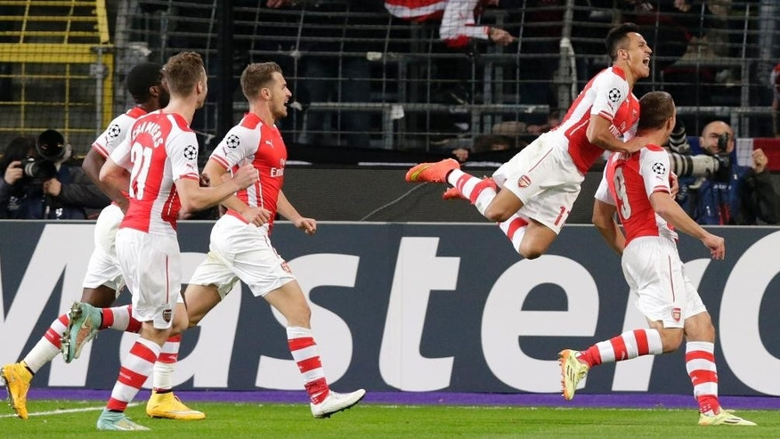 Arsenal's Lukas Podolski, right celebrates scoring the winning goal as teammate Arsenal's Alexis Sanchez leaps onto his back during the Group D Champions League match between Anderlecht and Arsenal at Constant Vanden Stock Stadium in Brussels, Belgium, Wednesday Oct. 22, 2014. Arsenal won the game 2-1.(AP Photo/Yves Logghe)