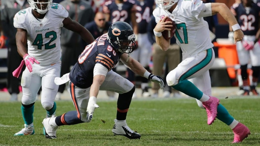 Miami Dolphins quarterback Ryan Tannehill (17) carries the ball past Chicago Bears linebacker Shea McClellin (50) during the second half of an NFL football game Sunday, Oct. 19, 2014 in Chicago. (AP Photo/Charles Rex Arbogast)