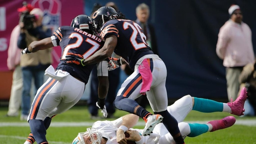 Chicago Bears cornerbacks Sherrick McManis (27) and Tim Jennings (26) knock down Miami Dolphins quarterback Ryan Tannehill during the second half of an NFL football game Sunday, Oct. 19, 2014 in Chicago. (AP Photo/Charles Rex Arbogast)