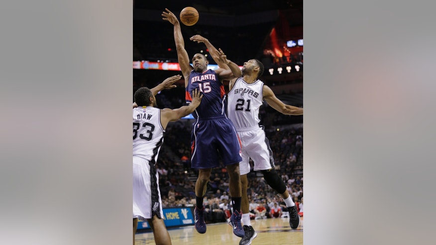 Atlanta Hawks' Al Horford (15) is blocked by San Antonio Spurs' Tim Duncan (21) while trying to score during the first half of an NBA preseason basketball game, Wednesday, Oct. 22, 2014, in San Antonio. Spurs' Boris Diaw (33) also defends on the play. (AP Photo/Eric Gay)