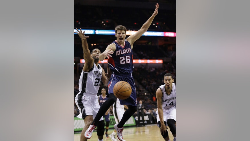 Atlanta Hawks' Kyle Korver (26) loses control of the ball as he is defended by San Antonio Spurs' Tim Duncan (21) during the first half of an NBA preseason basketball game, Wednesday, Oct. 22, 2014, in San Antonio. (AP Photo/Eric Gay)