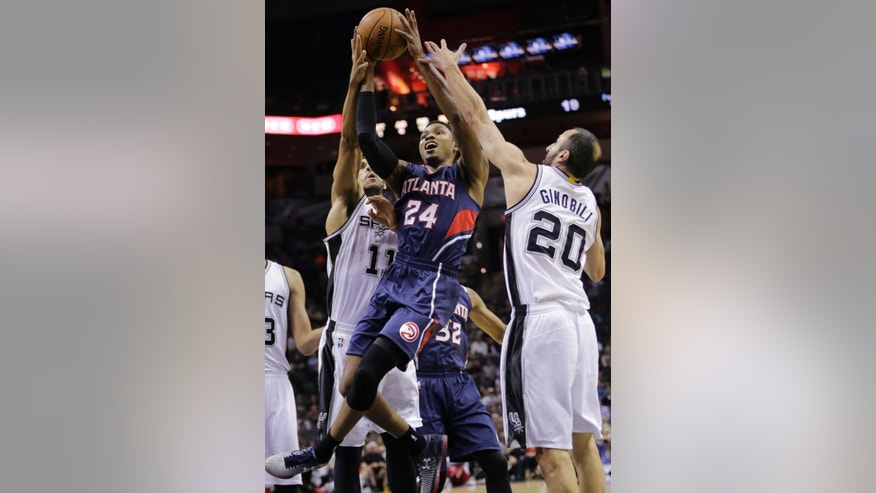 Atlanta Hawks' Kent Bazemore (24) is defended by San Antonio Spurs' Jeff Ayres (11) and Manu Ginobili (20) during the first half of an NBA preseason basketball game, Wednesday, Oct. 22, 2014, in San Antonio. (AP Photo/Eric Gay)