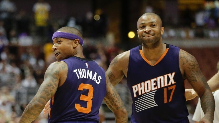 Phoenix Suns' Isaiah Thomas, left, and P.J. Tucker celebrate a game-tying basket by Thomas during the second half of a preseason NBA basketball game against the Los Angeles Lakers on Tuesday, Oct. 21, 2014, in Anaheim, Calif. The Suns won 114-108 in overtime. (AP Photo/Jae C. Hong)