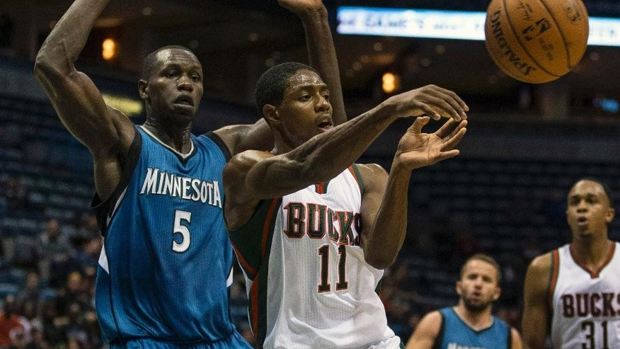 Milwaukee Bucks' Brandon Knight (11) passes the ball off while covered by Minnesota Timberwolves' Gorgui Dieng (5) during the first half of an NBA basketball game Wednesday, Oct. 22, 2014, in Milwaukee. (AP Photo/Tom Lynn)