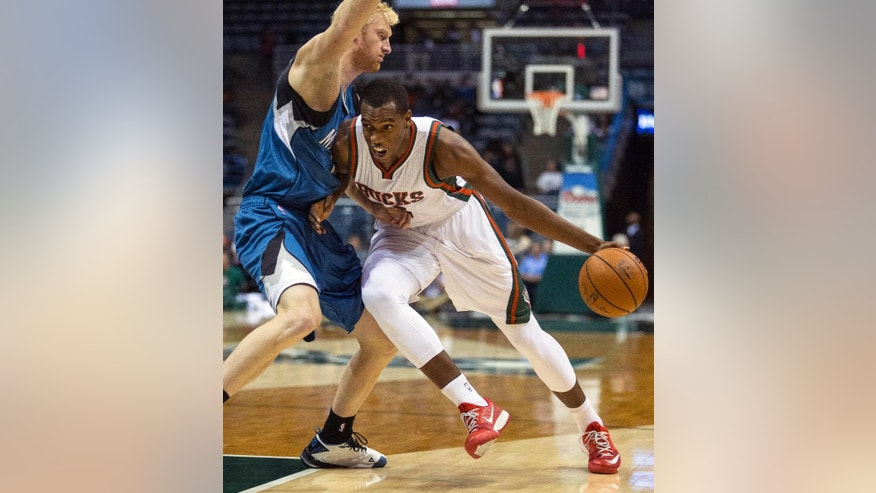 Milwaukee Bucks' Khris Middleton drives against Minnesota Timberwolves' Chase Budinger during the first half of an NBA basketball game Wednesday, Oct. 22, 2014, in Milwaukee. (AP Photo/Tom Lynn)