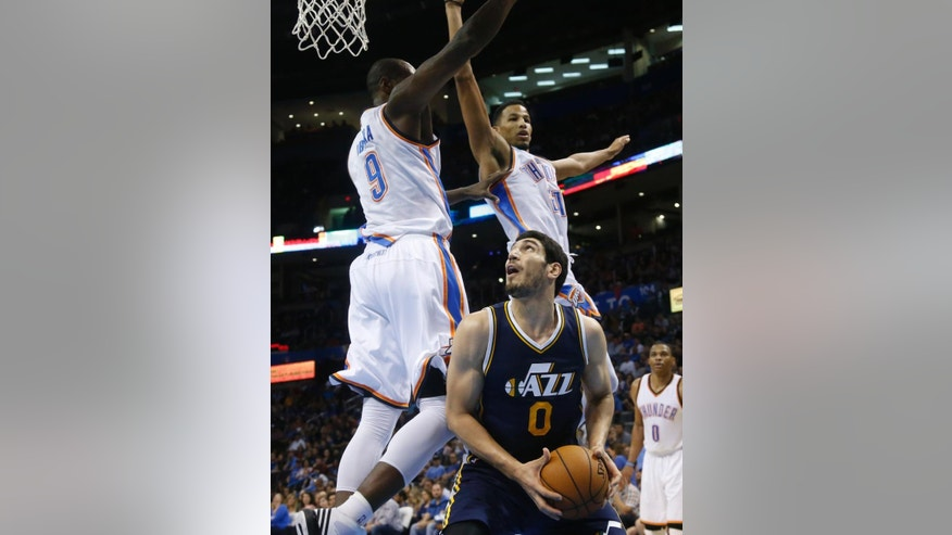 Utah Jazz center Enes Kanter (0) looks for a shot as Oklahoma City Thunder forward Serge Ibaka (9) and guard Andre Roberson (21) defend during the second quarter of a preseason NBA basketball game in Oklahoma City, Tuesday, Oct. 21, 2014. (AP Photo/Sue Ogrocki)