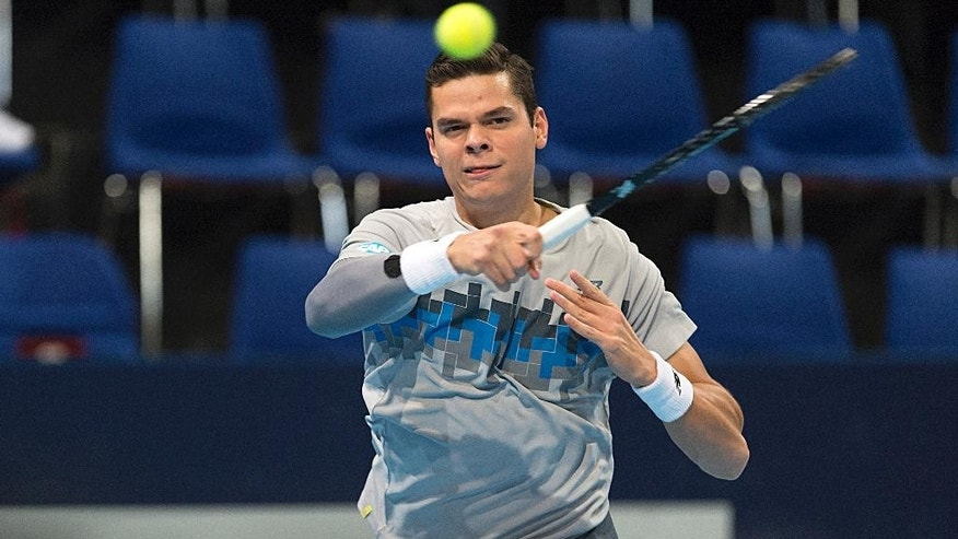 Canada's Milos Raonic returns a ball to Donald Young of the US during their match at the Swiss Indoors tennis tournament at the St. Jakobshalle in Basel, Switzerland, Oct. 23, 2014. (AP Photo/Keystone, Georgios Kefalas)