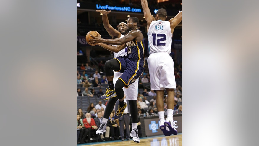 Indiana Pacers' Donald Sloan (15) drives between Charlotte Hornets' Gary Neal (12) and Al Jefferson (25) during the first half of a preseason NBA basketball game in Charlotte, N.C., Thursday, Oct. 23, 2014. (AP Photo/Chuck Burton)