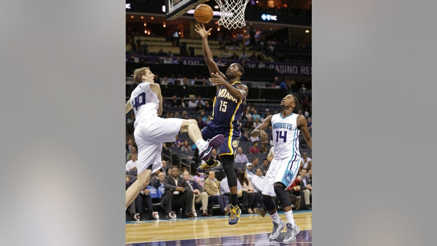 Indiana Pacers' Donald Sloan (15) drives between Charlotte Hornets' Cody Zeller (40) and Michael Kidd-Gilchrist (14) during the first half of a preseason NBA basketball game in Charlotte, N.C., Thursday, Oct. 23, 2014. (AP Photo/Chuck Burton)