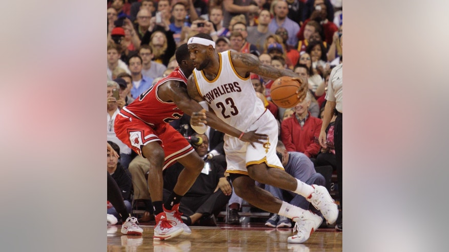 Cleveland Cavaliers' LeBron James, right, drives to the basket against Chicago Bulls' Tony Snell during the fourth quarter of an NBA preseason basketball game Monday, Oct. 20, 2014, in Columbus, Ohio. The Cavaliers beat the Bulls 107-98. (AP Photo/Jay LaPrete)