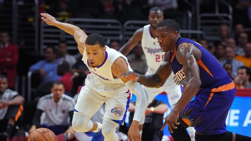 Los Angeles Clippers guard Jared Cunningham, left, and Phoenix Suns guard Eric Bledsoe go after a loose during the first half of a preseason NBA basketball game, Wednesday, Oct. 22, 2014, in Los Angeles. (AP Photo/Mark J. Terrill)