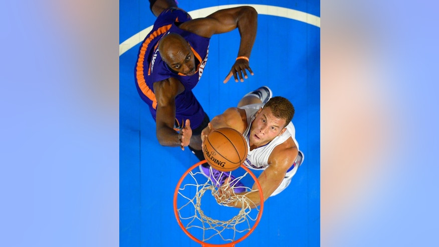 Los Angeles Clippers forward Blake Griffin, below, puts up a shot as Phoenix Suns forward Anthony Tolliver defends during the first half of a preseason NBA basketball game, Wednesday, Oct. 22, 2014, in Los Angeles.   (AP Photo/Mark J. Terrill)