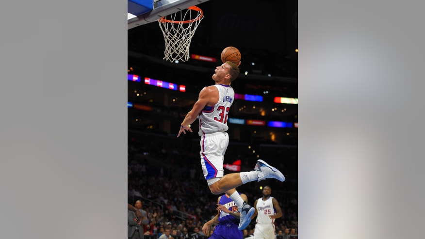 Los Angeles Clippers forward Blake Griffin goes up for a dunk as Phoenix Suns guard Gerald Green and Clippers guard Reggie Bullock watch during the first half of a preseason NBA basketball game, Wednesday, Oct. 22, 2014, in Los Angeles. (AP Photo/Mark J. Terrill)