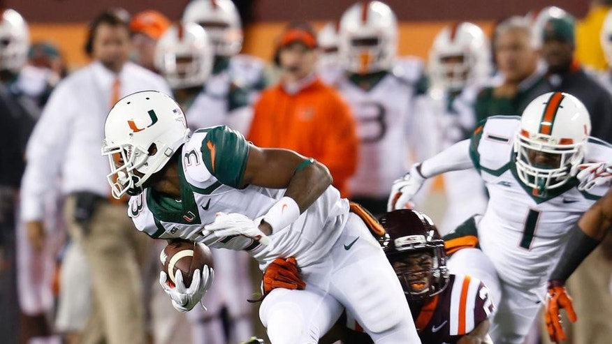 Miami wide receiver Stacy Coley (3) breaks the tackle of Miami defensive back Ray Lewis III (20) during the first half of an NCAA college football game in Blacksburg, Va., Thursday, Oct. 23, 2014. (AP Photo/Steve Helber)