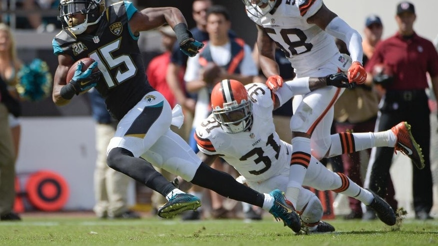 Jacksonville Jaguars wide receiver Allen Robinson (15) runs past Cleveland Browns strong safety Donte Whitner (31) and inside linebacker Chris Kirksey (58) for a touchdown during the first half of an NFL football game in Jacksonville, Fla., Sunday, Oct. 19, 2014. (AP Photo/Phelan M. Ebenhack)