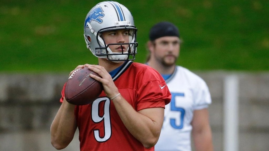 Detroit Lions quarterback Matthew Stafford, center, prepares to throw a ball during a training session at Pennyhill Park Hotel in Bagshot, England, Thursday, Oct. 23, 2014. The Atlanta Falcons will play the Detroit Lions in an NFL football game at London's Wembley Stadium on Sunday. (AP Photo/Matt Dunham)