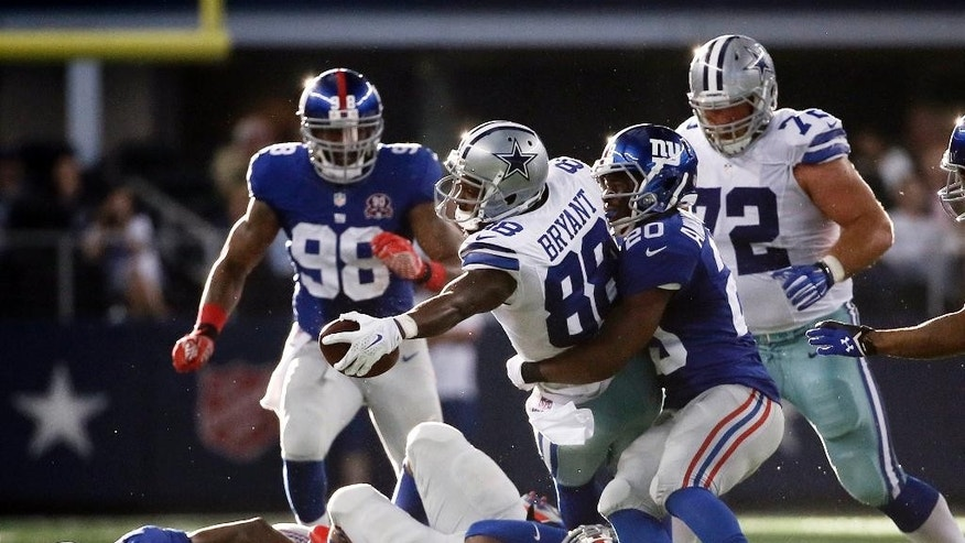 Dallas Cowboys' Dez Bryant (88) leans out for extra yardage after grabbing a pass as New York Giants' Prince Amukamara (20) defends during the second half of an NFL football game, Sunday, Oct. 19, 2014, in Arlington, Texas. The Giants' Damontre Moore (98), Jameel McClain (53), Johnathan Hankins (95) and the Cowboys' Travis Frederick (72) are near on the play. (AP Photo/Brandon Wade)