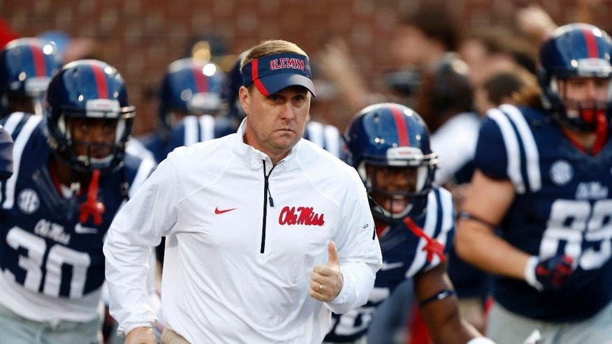 Mississippi coach Hugh Freeze run onto the field before an NCAA college football game against Tennessee in Oxford, Miss., Saturday, Oct. 18, 2014. (AP Photo/Rogelio V. Solis)