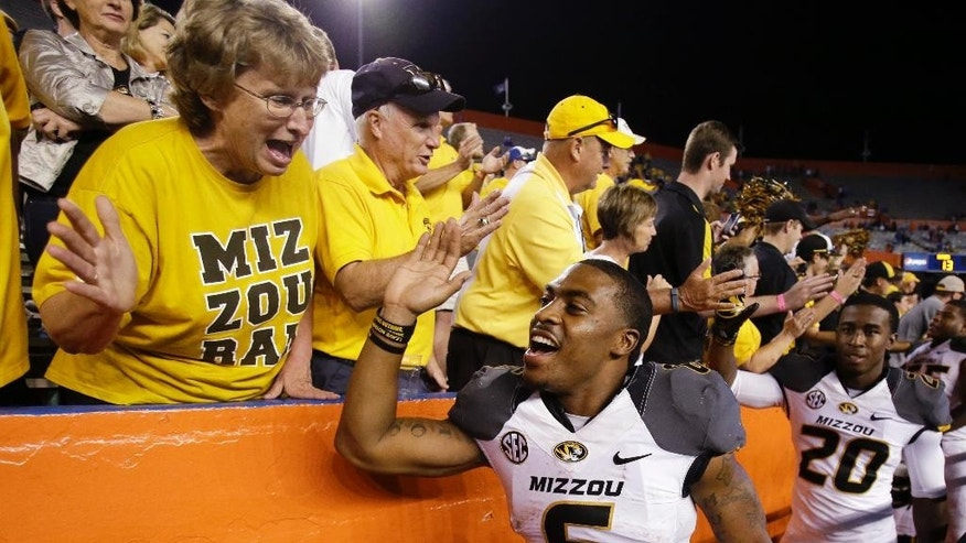 Missouri running backs Marcus Murphy (6) and Trevon Walters (20) celebrate with fans after Missouri defeated Florida 42-13 in an NCAA college football game in Gainesville, Fla., Saturday, Oct. 18, 2014.  (AP Photo/John Raoux)