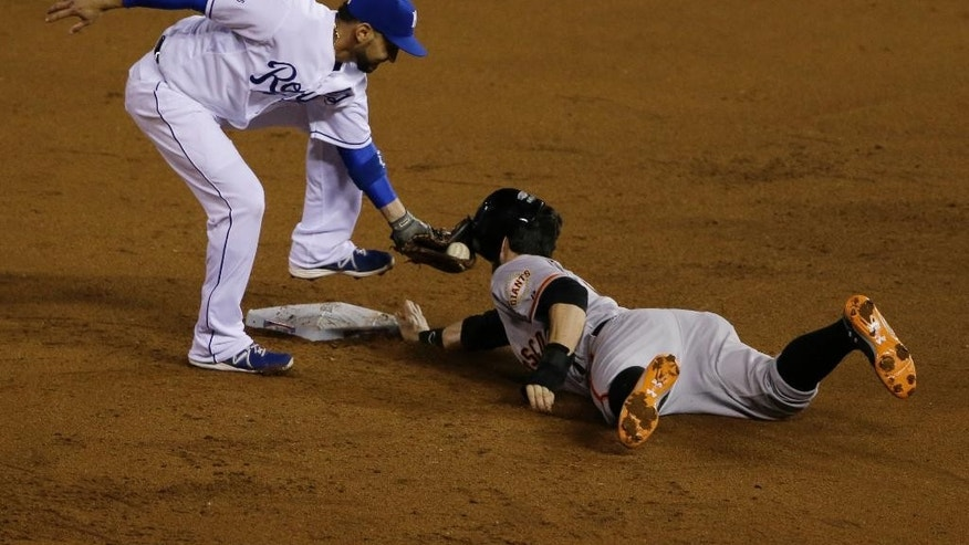 Kansas City Royals Omar Infante tags out San Francisco Giants Brandon Belt after he was caught off base during the fourth inning of Game 2 of baseball's World Series Wednesday, Oct. 22, 2014, in Kansas City, Mo. (AP Photo/Orlin Wagner)