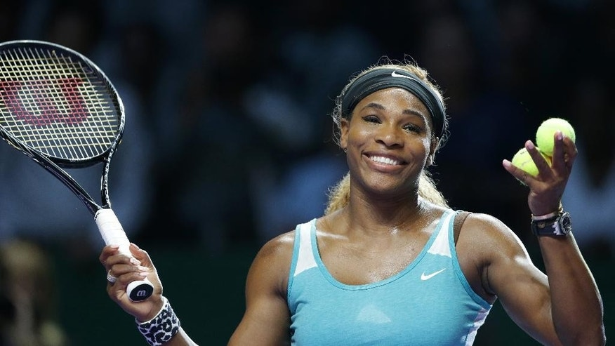Serena Williams of the US reacts after hitting an autographed ball into the crowd following her win over Canada's Eugenie Bouchard during their singles match at the WTA tennis finals in Singapore,Thursday, Oct. 23, 2014. (AP Photo/Mark Baker)