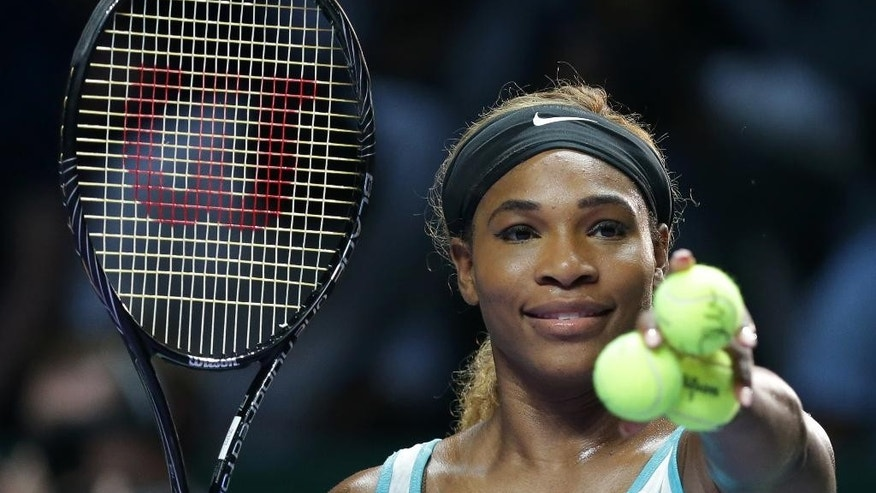 Serena Williams of the US prepares to hit autographed balls into the crowd following her win over Canada's Eugenie Bouchard during their singles match at the WTA tennis finals in Singapore,Thursday, Oct. 23, 2014. (AP Photo/Mark Baker)