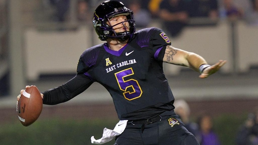 East Carolina quarterback Shane Carden (5) prepares to launch a pass against Connecticut during an NCAA college football game in Greenville, N.C., Thursday, Oct. 23, 2014. (AP Photo/Ted Richardson)