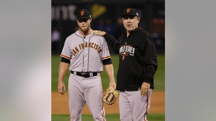 San Francisco Giants Bruce Bochy stands with pitcher Hunter Strickland before relieving him with Jeremy Affeldt during the sixth inning of Game 2 of baseball's World Series against the Kansas City Royals Wednesday, Oct. 22, 2014, in Kansas City, Mo. (AP Photo/Matt Slocum)
