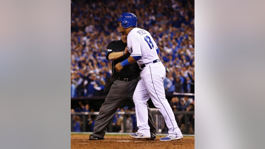 Home plate umpire Eric Cooper holds back Kansas City Royals Salvador Perez as he argues with San Francisco Giants pitcher Hunter Strickland during the sixth inning of Game 2 of baseball's World Series Wednesday, Oct. 22, 2014, in Kansas City, Mo. (AP Photo/Matt Slocum)