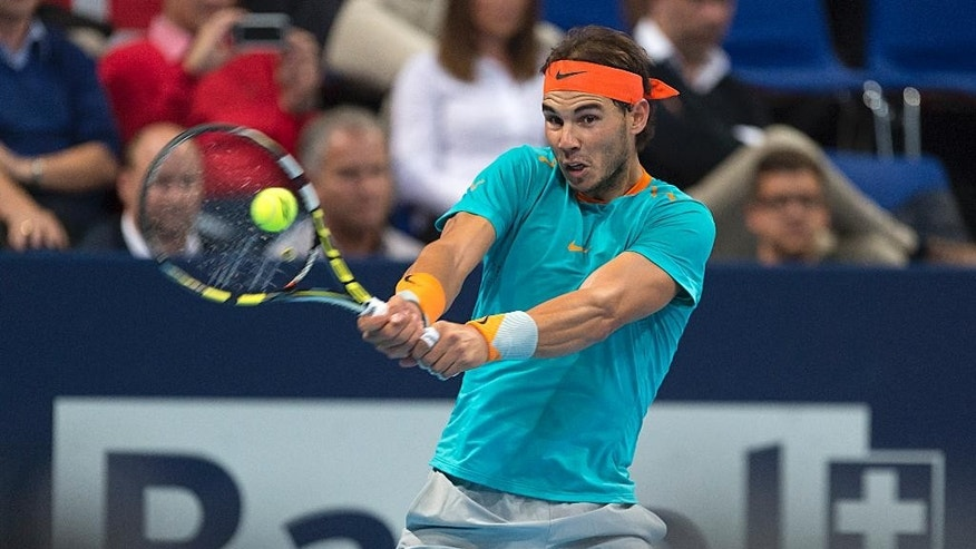 Spain's Rafael Nadal returns a ball to France's Pierre-Hugues Herbert during their round of sixteen match at the Swiss Indoors tennis tournament at the St. Jakobshalle in Basel, Switzerland, on Wednesday, Oct. 22, 2014.  (AP Photo/Keystone,Georgios Kefalas)