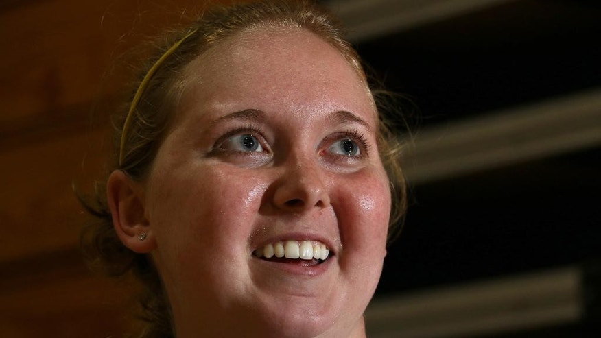 Lauren Hill smiles as she talks with reporters after practicing with her NCAA college basketball team at Mount St. Joseph University in Cincinnati on Thursday, Oct. 23, 2014. The NCAA allowed Mount St. Joseph's season opener to be moved up to Nov. 2, so that Hill, who has an inoperable brain tumor, will be able to play in a college basketball game. (AP Photo/Tom Uhlman)