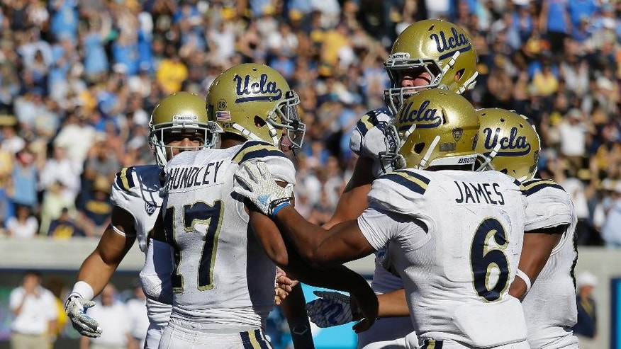 UCLA quarterback Brett Hundley (17) is greeted by his teammates after scoring a touchdown during the third quarter of an NCAA college football game against California on Saturday, Oct. 18, 2014, in Berkeley, Calif. At right is UCLA running back Jordon James (6).UCLA won 36-34. (AP Photo/Eric Risberg)