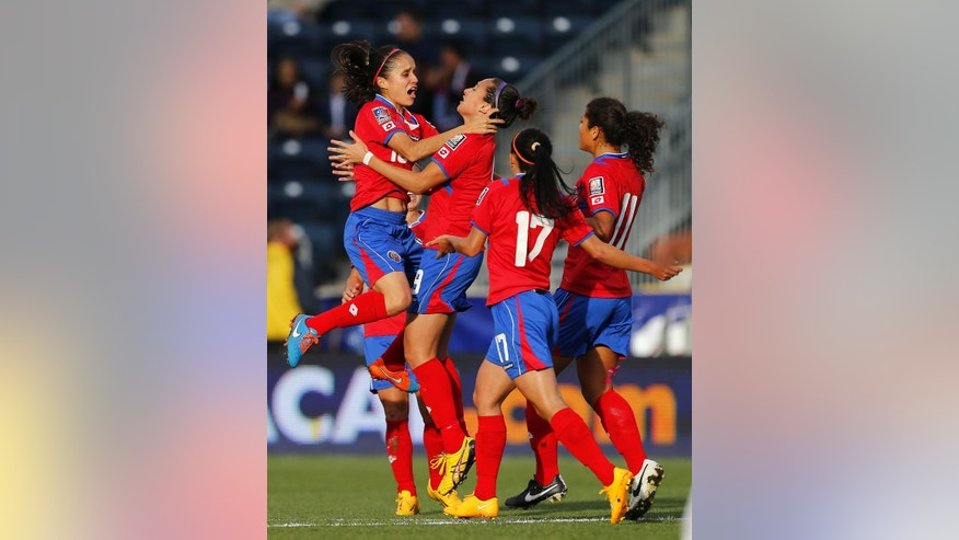 Costa Rica midfielder Katherine Alvarado (16) jumps into the arms of forward Carolina Venegas (9) after Venegas' goal in the first half against Trinidad and Tobago during a CONCACAF semifinal soccer match in Philadelphia, Pa., Friday, Oct. 24, 2014. (AP Photo/Rich Schultz)
