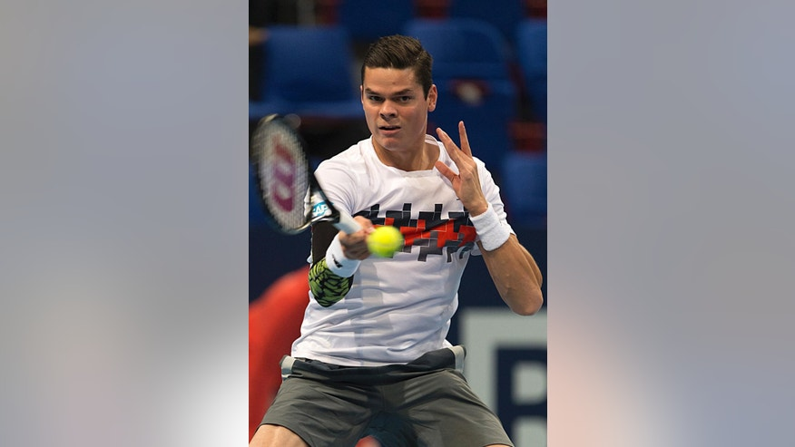 Canada's Milos Raonic returns a ball to Belgium's David Goffin during their quarter final match at the Swiss Indoors tennis tournament at the St. Jakobshalle in Basel, Switzerland, Friday, Oct. 24, 2014. (AP Photo/Keystone, Georgios Kefalas)