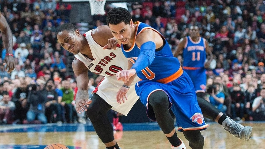 Toronto Raptors' DeMar DeRozan, left, and New York Knicks' Shane Larkin lunge for the ball during second-quarter NBA preseason basketball game action in Montreal, Friday, Oct. 24, 2014. (AP Photo/The Canadian Press, Graham Hughes)