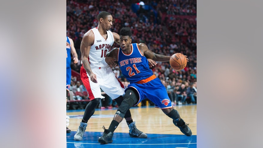 New York Knicks' Iman Shumpert (21) drives to the net as Toronto Raptors' DeMar DeRozan defends during third-quarter NBA preseason basketball game action in Montreal, Friday, Oct. 24, 2014. (AP Photo/The Canadian Press, Graham Hughes)