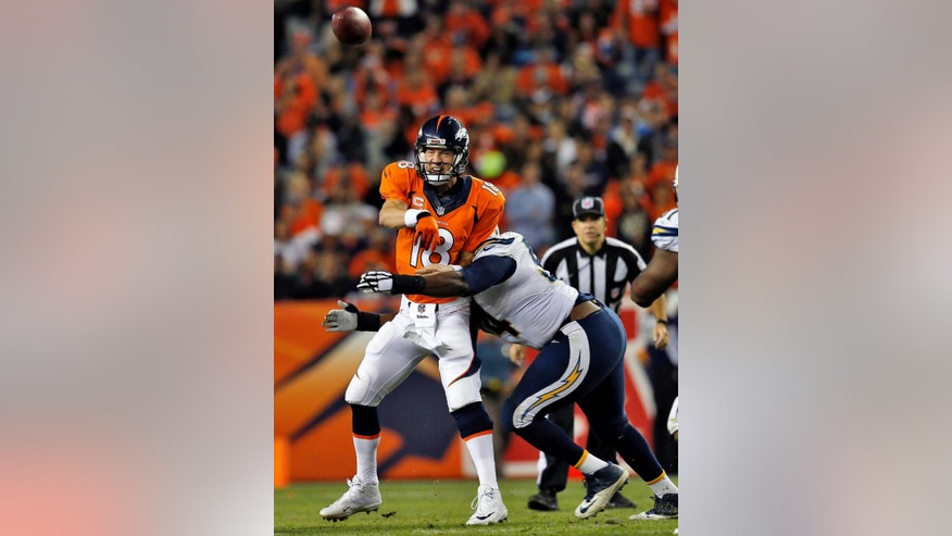 Denver Broncos quarterback Peyton Manning (18) gets a throw off as he is hit by San Diego Chargers defensive end Corey Liuget during the second half of an NFL football game, Thursday, Oct. 23, 2014, in Denver. (AP Photo/Joe Mahoney)