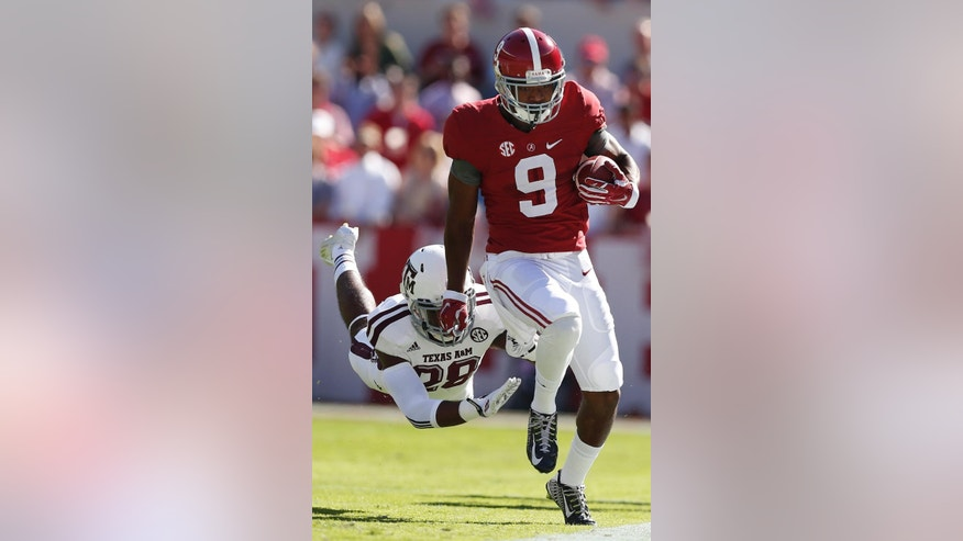 Alabama wide receiver Amari Cooper (9) runs the ball as Texas A&M defensive back Victor Davis (28) attempts a tackle during the first half of an NCAA college football game on Saturday, Oct, 18, 2014, in Tuscaloosa, Ala. (AP Photo/Brynn Anderson)