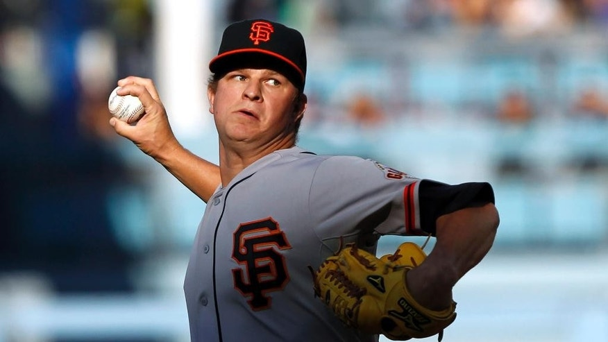 File - In this April 6, 2014, file photo, San Francisco Giants starting pitcher Matt Cain throws against the Los Angeles Dodgers in the first inning of a baseball game in Los Angeles. Cain has been the workhorse of the San Francisco Giants' pitching staff for years, but the elbow injury ended his season and left him rooting for his teammates in the World Series. (AP Photo/Alex Gallardo, File)