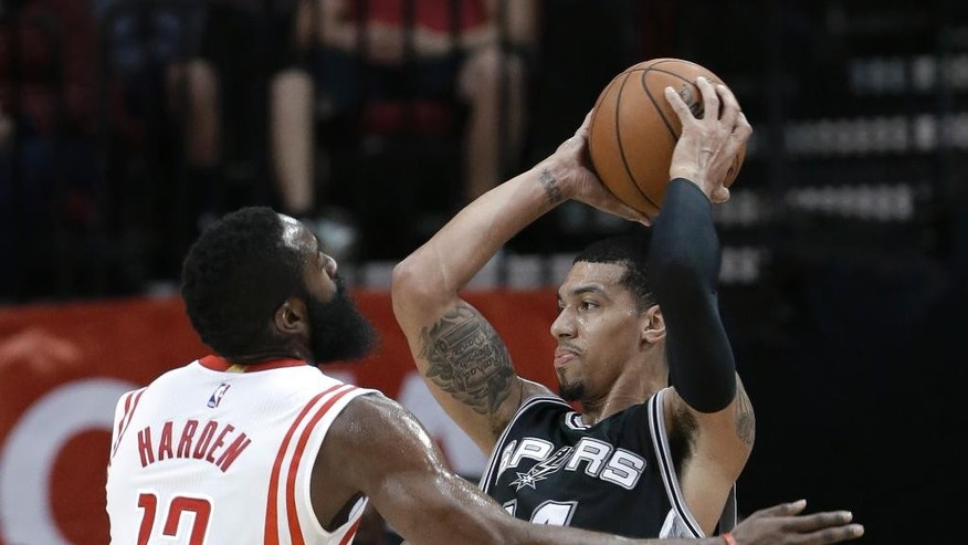 San Antonio Spurs' Danny Green (14) looks to pass the ball past Houston Rockets' James Harden (13) during the first half of an NBA exhibition basketball game Friday, Oct. 24, 2014, in Houston. (AP Photo/Pat Sullivan)