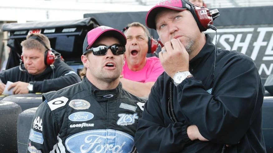 Ricky Stenhouse Jr., left, talks with crew chief, Mike Kelley, right, as they look at the tally board during qualifying for Sunday's Sprint Cup Series auto race at Martinsville Speedway in Martinsville, Va., Friday, Oct. 24, 2014. (AP Photo/Steve Helber)