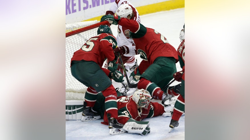 Minnesota Wild goalie Darcy Kuemper sprawls on the ice, bottom, as teammates try to keep Arizona Coyotes' Brandon McMillan, top in white, at bay during the first period of an NHL hockey game, Thursday, Oct. 23, 2014, in St. Paul, Minn. (AP Photo/Jim Mone)