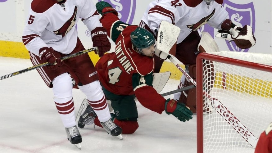 Minnesota Wild's Justin Fontaine, center, falls as he chases the puck between Arizona Coyotes' Connor Murphy, left, and goalie Mike Smith during the first period of an NHL hockey game, Thursday, Oct. 23, 2014, in St. Paul, Minn. (AP Photo/Jim Mone)