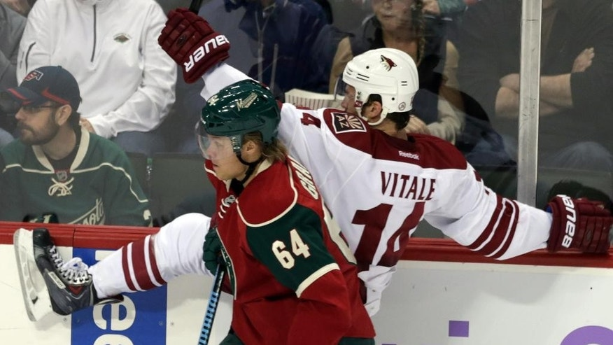 Minnesota Wild's Mikael Granlund, left, of Finland, checks Arizona Coyotes' Joe Vitale into the boards during the first period of an NHL hockey game, Thursday, Oct. 23, 2014, in St. Paul, Minn. (AP Photo/Jim Mone)