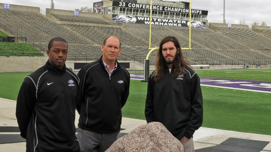 In this Oct. 21, 2014, photo, Wisconsin-Whitewater coach Lance Leipold poses for a picture at Perkins Stadium with running back Ryan Givens, left, and receiver Jake Kumerow, right, on Tuesday, Oct. 21, 2014 in Whitewater, Wis. The Division III coach reached 100 career wins in 106 games, the fastest to the 100-win plateau in NCAA history. (AP Photo/Genaro C. Armas)